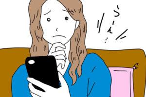 家のソファでスマホを見て悩む女性